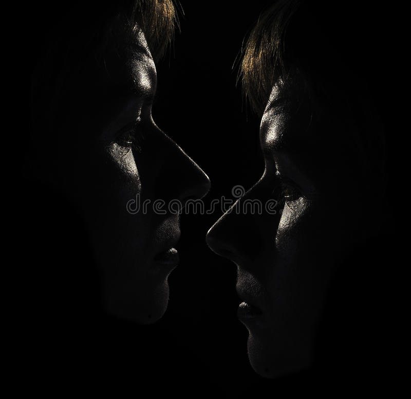 Two Women's Faces in the Dark stock photo