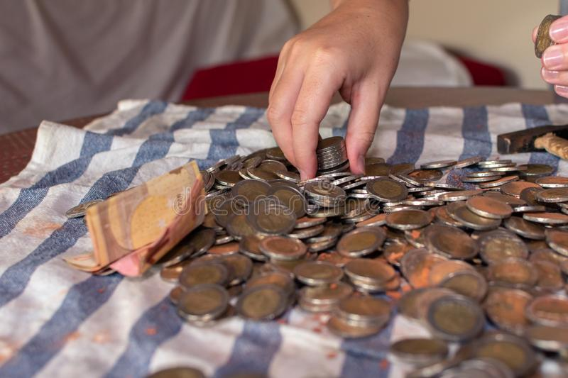 Two women`s hands selecting many coins scattered on a table royalty free stock photography