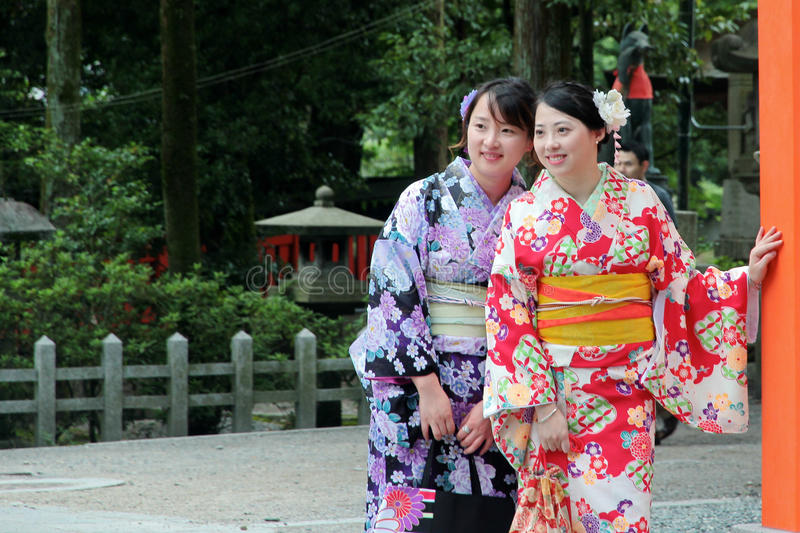 Two women`s kimonos post and smile for photo within shrine. Kyoto,Japan-June 26,Two Women`s kimonos post and smile for photo within Fushimi Inari shrine on June stock image