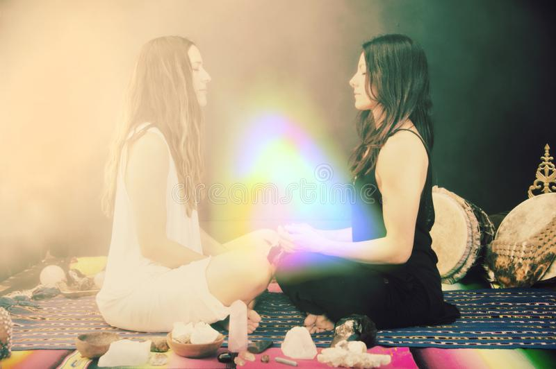 Sage Women In Crystal Rainbow Ceremony. Two Women in a sacred shamanic healing ceremony with Sage Smudge, Rose Quartz, and other sacred stones royalty free stock photography