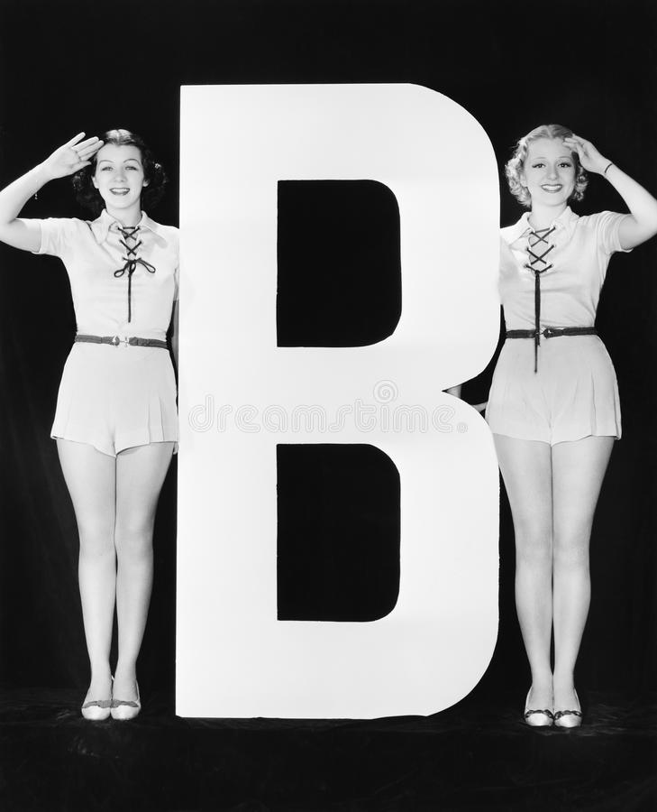 Two women saluting with huge letter B. (All persons depicted are no longer living and no estate exists. Supplier grants that there will be no model release stock photos