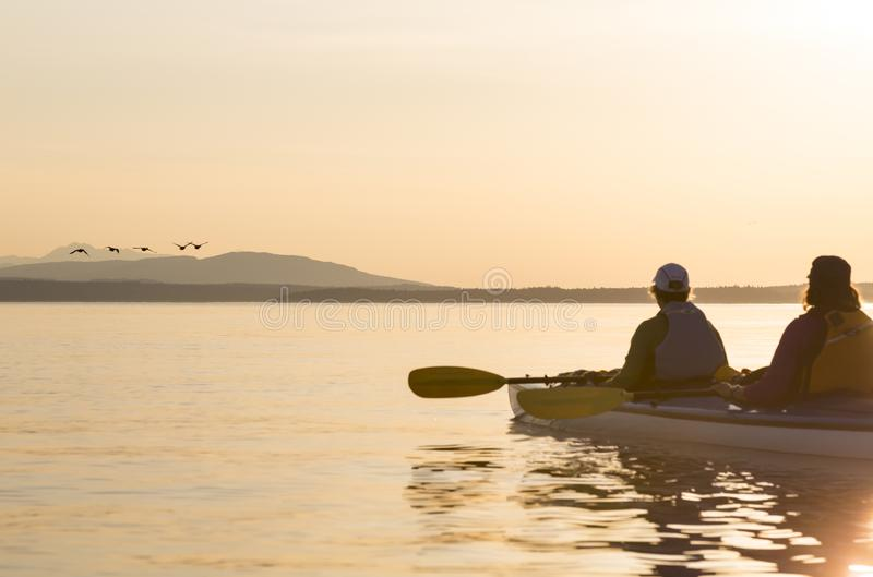 Two women in a sea kayak bird watching. People enjoying healthy lifestyles, nature and wildlife royalty free stock photography