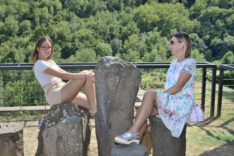 Two women seating on stone with forest in the background royalty free stock photography