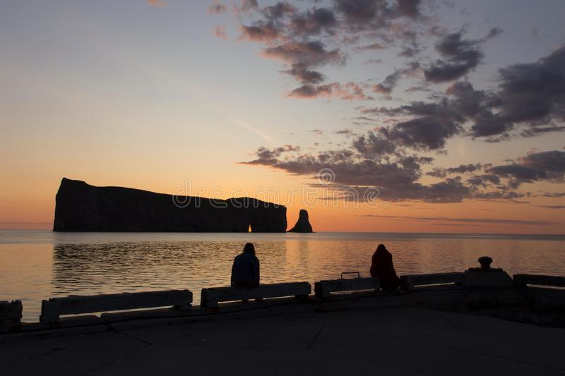 Two women seen in silhouette sitting on the Percé pier watching the sun rising behind the famous rock royalty free stock images