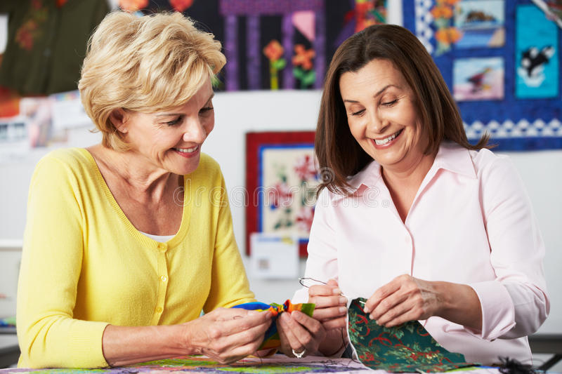 Two Women Sewing Quilt Together royalty free stock photos