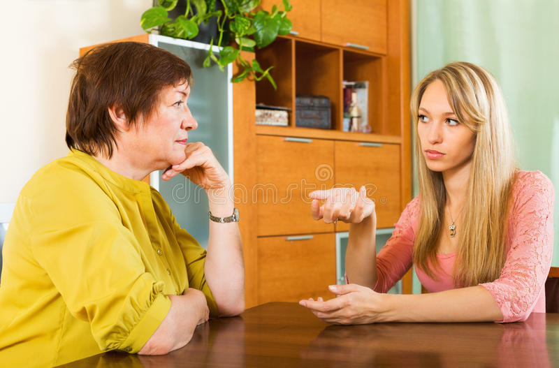 Two women sharing bad news. Mature female with adult daughter sharing bad news at home stock image
