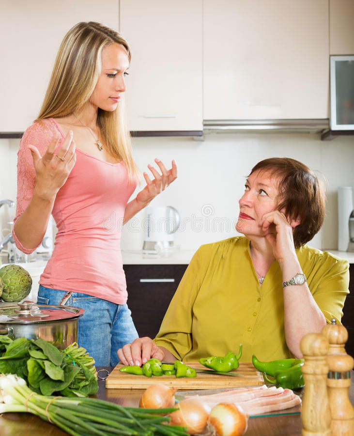 Two women sharing bad news. Sad mature women with angry adult daughter sharing bad news in kitchen at home stock image