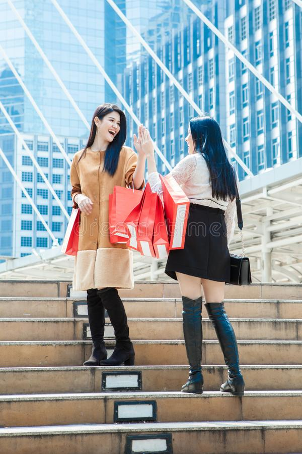 Two woman with shopping bags greeting together outdoor city street. royalty free stock photo