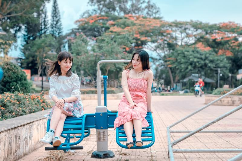 Two Women Sitting in Blue Park Ride stock images