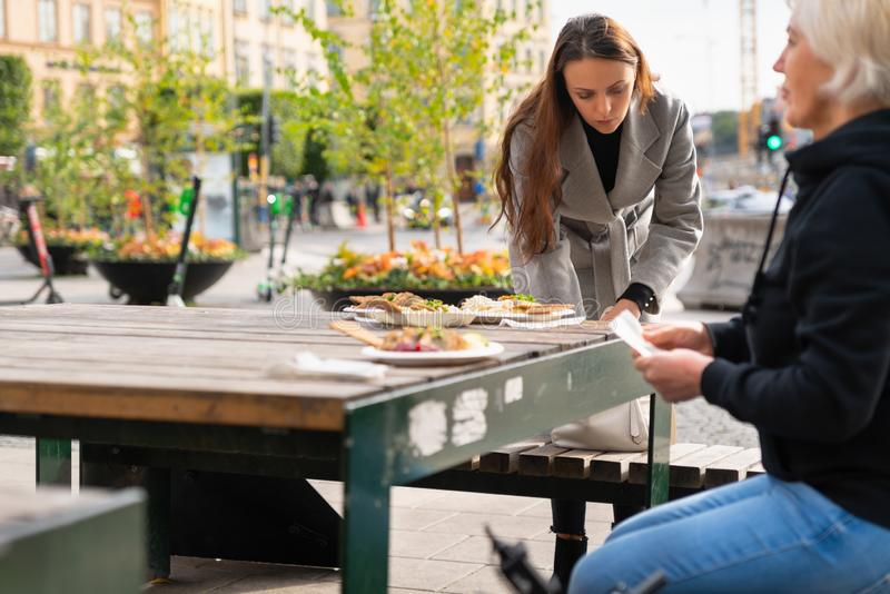 Two women sitting down for a meal outdoors royalty free stock images