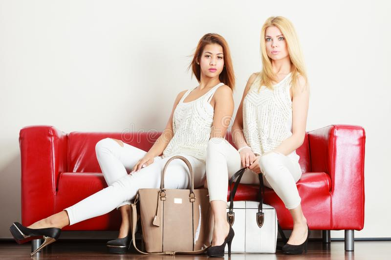 Two women sitting on sofa presenting bags royalty free stock photography