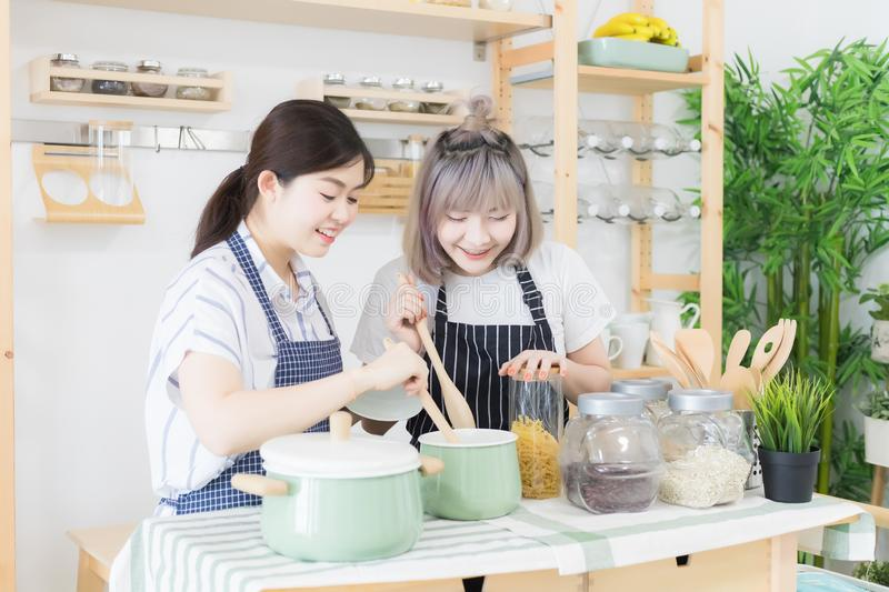 Two women are smiling, are tasting food and cooking on a table full of kitchen utensils. There is a backdrop of condiments. Two women are smiling, are tasting royalty free stock photos