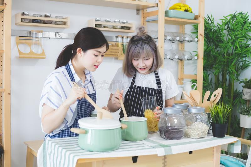 Two women are smiling, are tasting food and cooking on a table full of kitchen utensils. There is a backdrop of condiments. And spices in the kitchen in royalty free stock photo