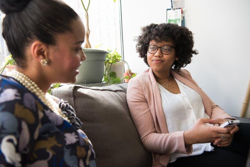 Two Women on Sofa Chatting royalty free stock photos