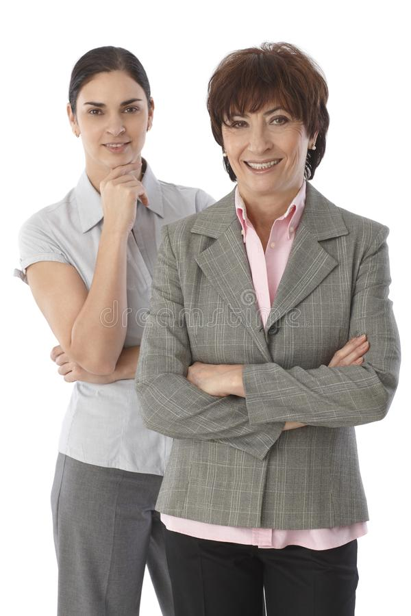 Two women standing arms crossed smiling royalty free stock images