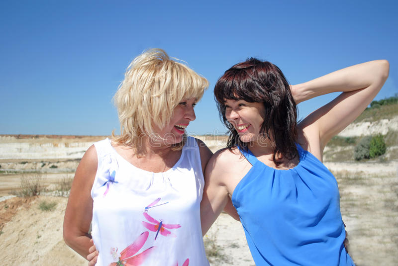 Two women standing and laughing royalty free stock image