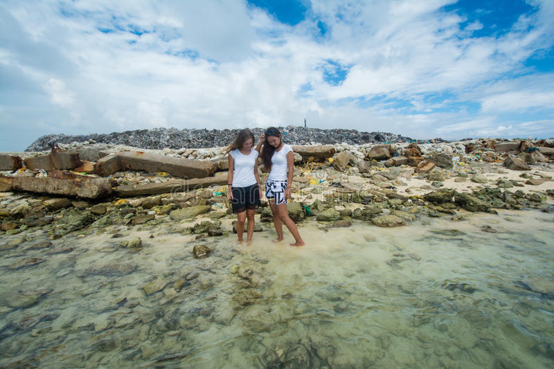 Two women standing in the ocean near garbage dump and holding hands stock photography