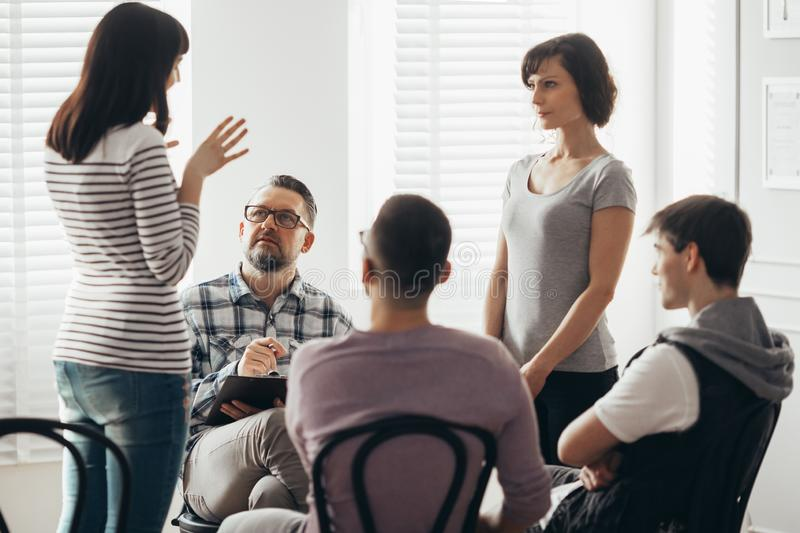 Two women standing and talking during group therapy with psychologist. Two women talking during group therapy with psychologist stock photo