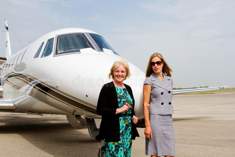 Two women standing on tarmac. By jet stock image