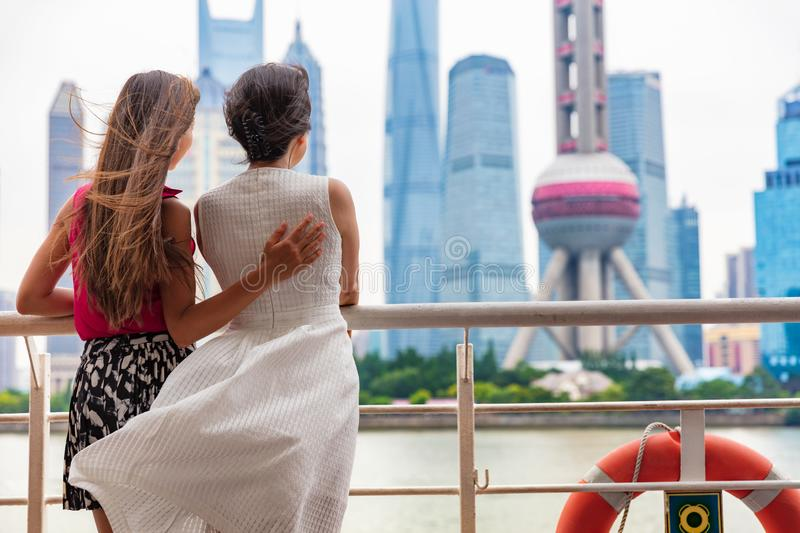Two women taking the ferry in Shanghai city, China, crossing the Bund river looking at the view of famous pearl tv tower, landmark. Travel people lifestyle royalty free stock photos