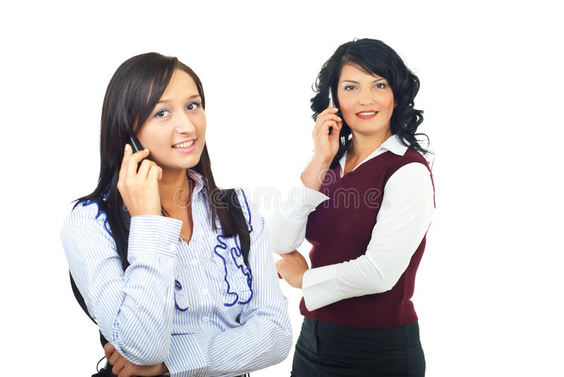 Two women talking by cell phones. And smiling isolated on white background, check also stock photography