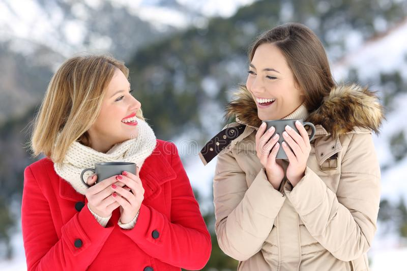 Two women talking with coffee cups in winter. Two happy women talking holding coffee cups in winter holiday in the mountain stock image