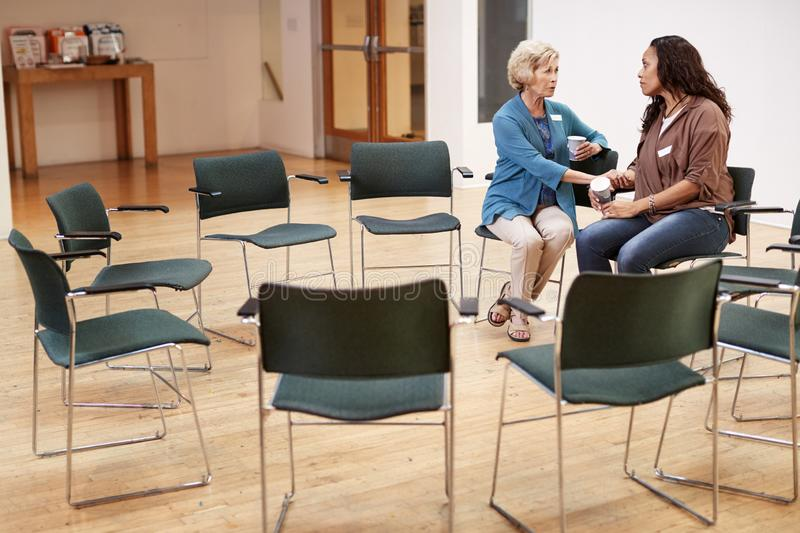 Two Women Talking After Meeting In Community Center stock photos