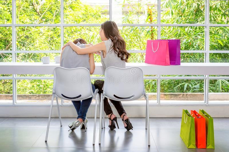 Two women talking about problems at coffee shop. unhappy girl support her girlfriend. Sad Female sitting in the room. Friends do. Not give up. Sad girl and royalty free stock image
