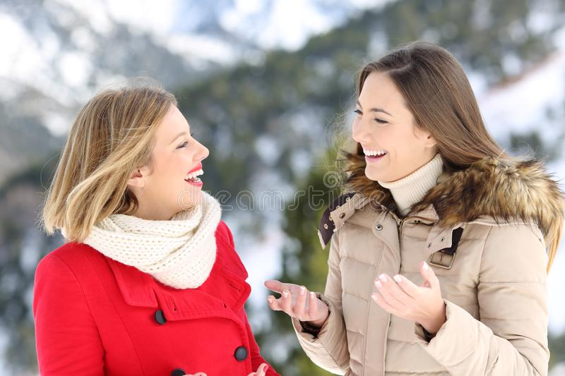 Two women talking in winter holiday in the mountain. Two happy women warmly clothed talking in winter holiday in the mountain royalty free stock image