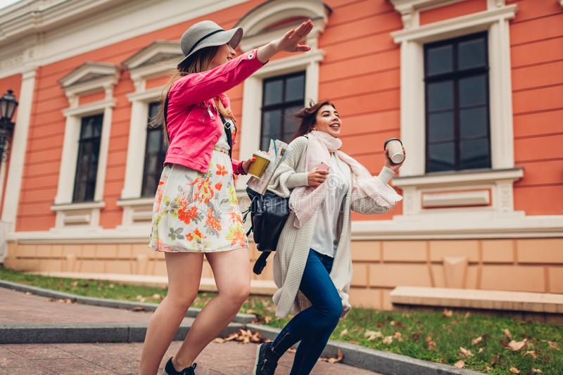 Two women tourists running to catch a cab in Odessa. Happy friends travelers laughing while hurrying up royalty free stock images