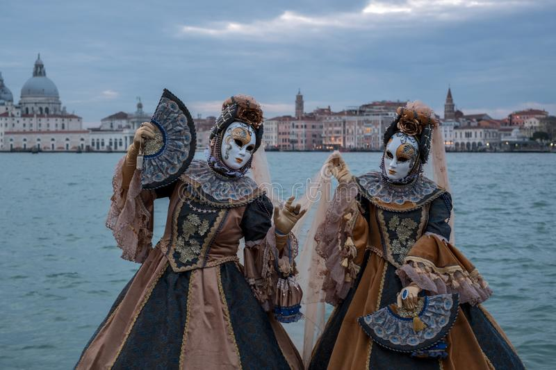 Two women in traditional costumes standing in front of the the Grand Canal during the Venice Carnival. Basilica di Santa Maria della Salute is in the stock photography