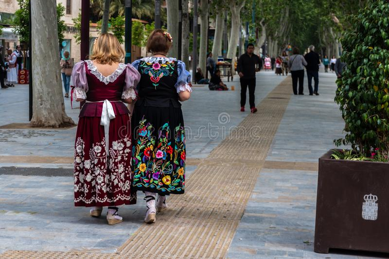 Two women in traditional festive embroidered dresses during the spring festival of Bando de la Huerta in royalty free stock images