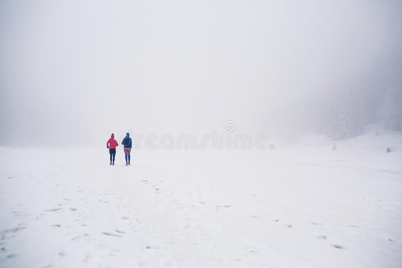 Two women trail running on snow in winter mountains royalty free stock photo