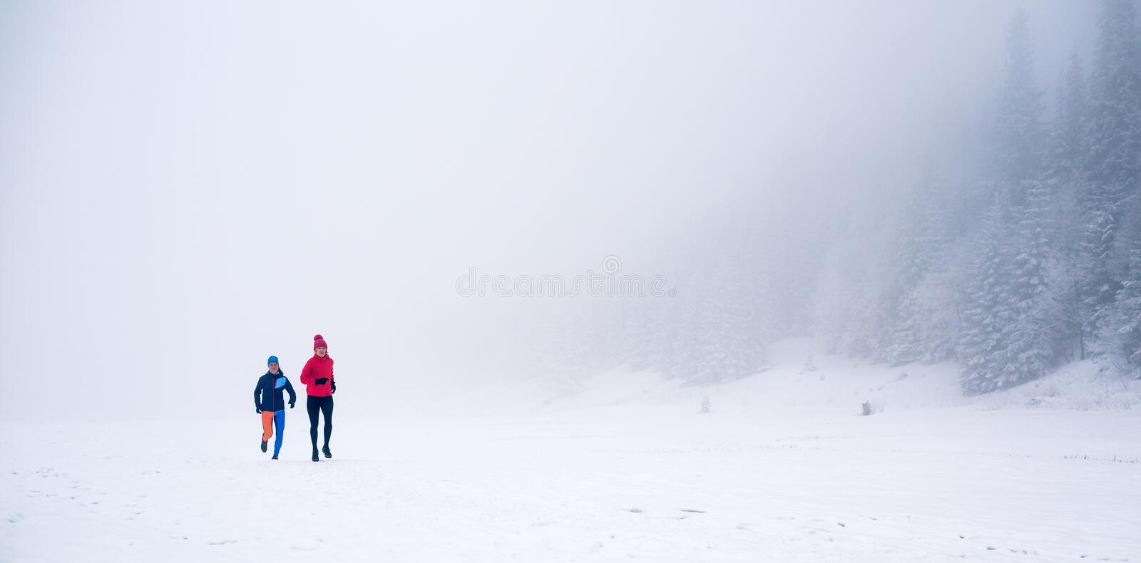 Two women trail running on snow in winter mountains stock photography