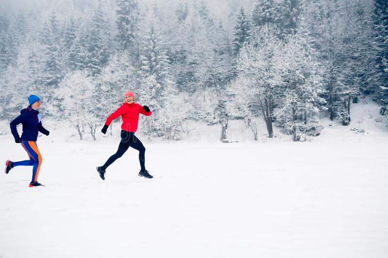 Two women trail running on snow in winter mountains royalty free stock images