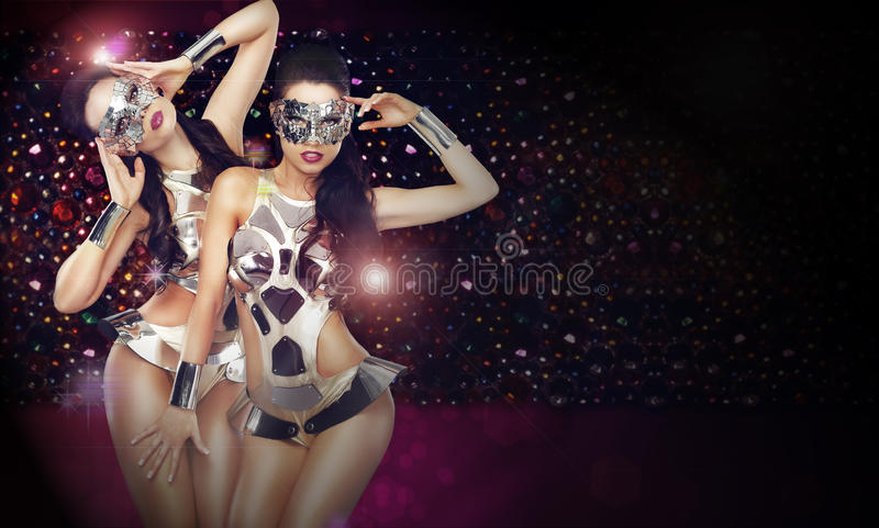 Two Women in Trendy Stagy Costumes Dancing over Abstract Background. Disco Club. Two Women in Trendy Stagy Costumes Dancing over Abstract Background royalty free stock image