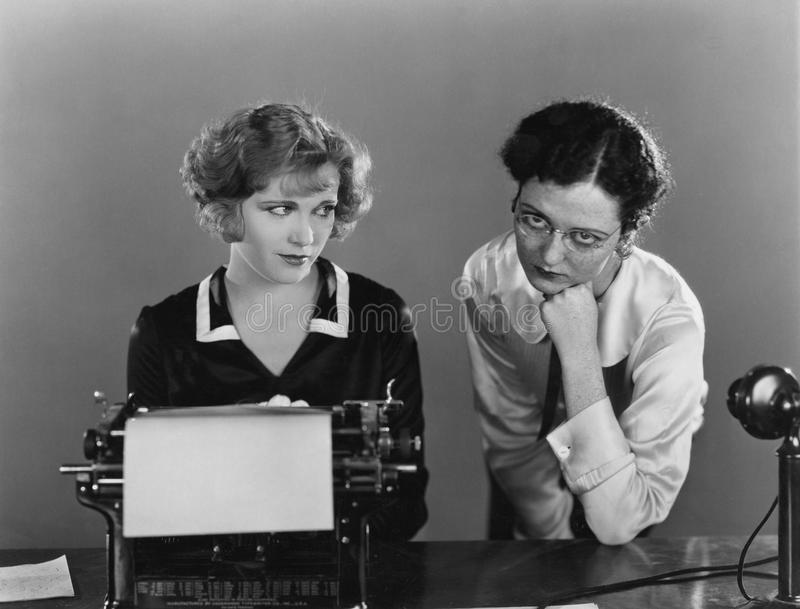 Two women with typewriter royalty free stock images