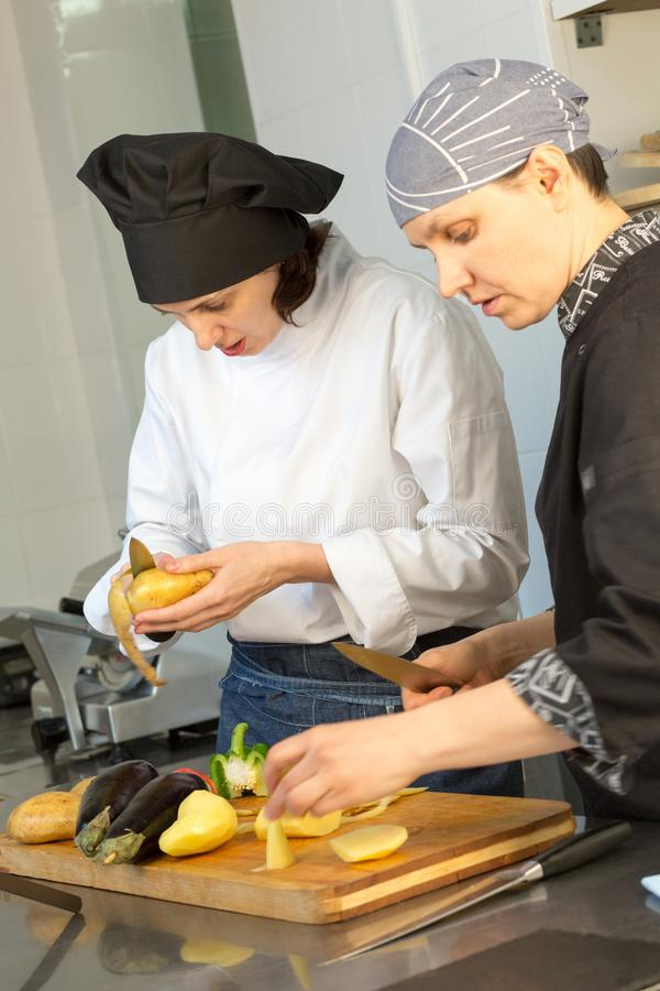 Two women in uniform cut vegetables: potatoes and eggplants in the kitchen of the restaurant. stock photography