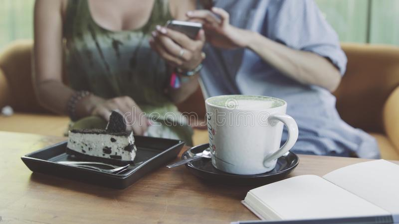 Two Women using digital tablet drinking coffee in cafe stock photo