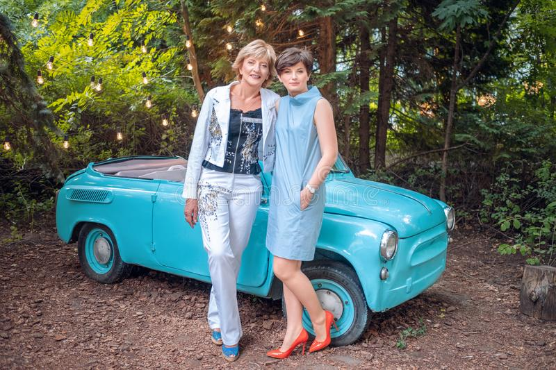 Two women in a vintage car. happy senior mother and adult daughter stand by a retro convertible stock photo