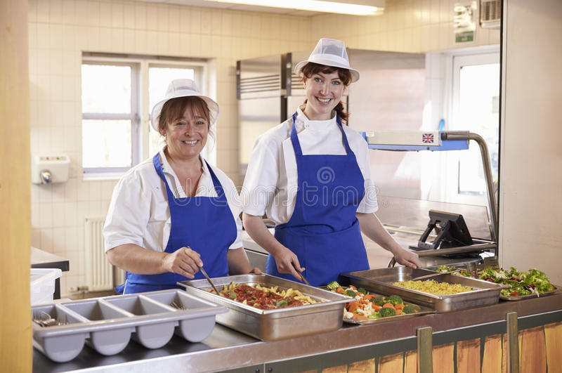 Two women waiting to serve lunch in a school cafeteria stock images