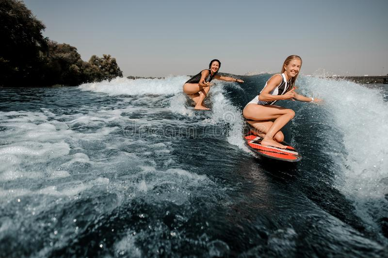 Two women wakesurfing on boards down the blue wave. Two happy women wakesurfing on boards down the blue wave on hot sunny day stock photos