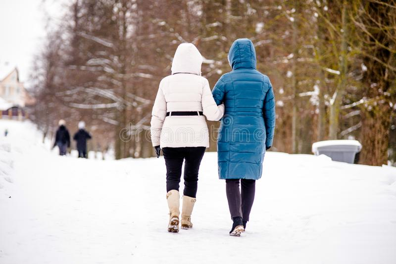 Two women walk along the path. In the winter Park royalty free stock photography
