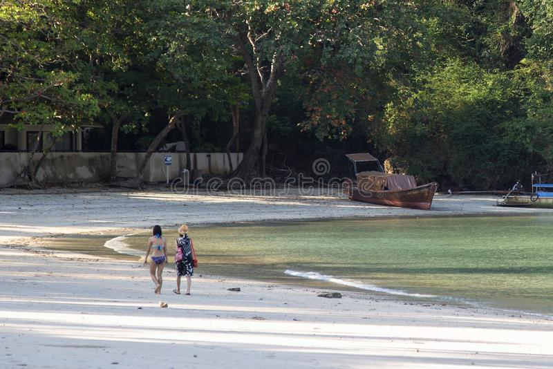 Two women walk along the sandy beach in the morning.  royalty free stock photos