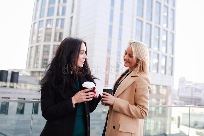 Two women walk in the city, drink coffee. And enjoy the rest royalty free stock images