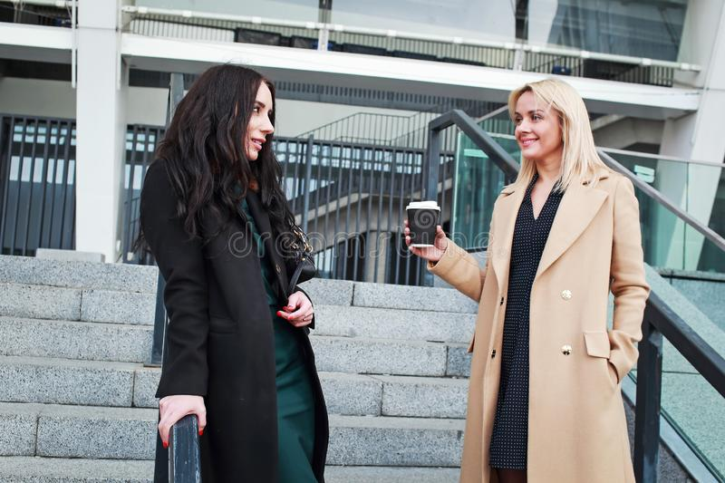 Two women walk in the city, drink coffee. And enjoy the rest royalty free stock photos