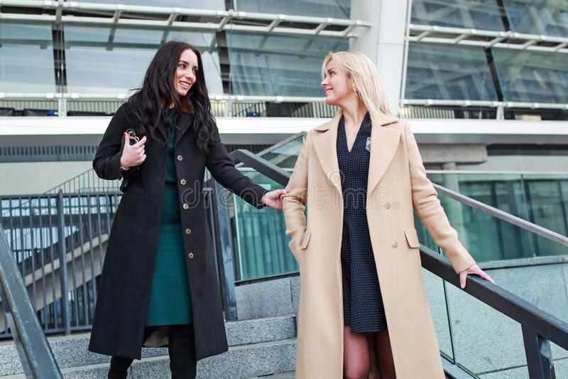 Two women walk in the city, drink coffee. And enjoy the rest stock images
