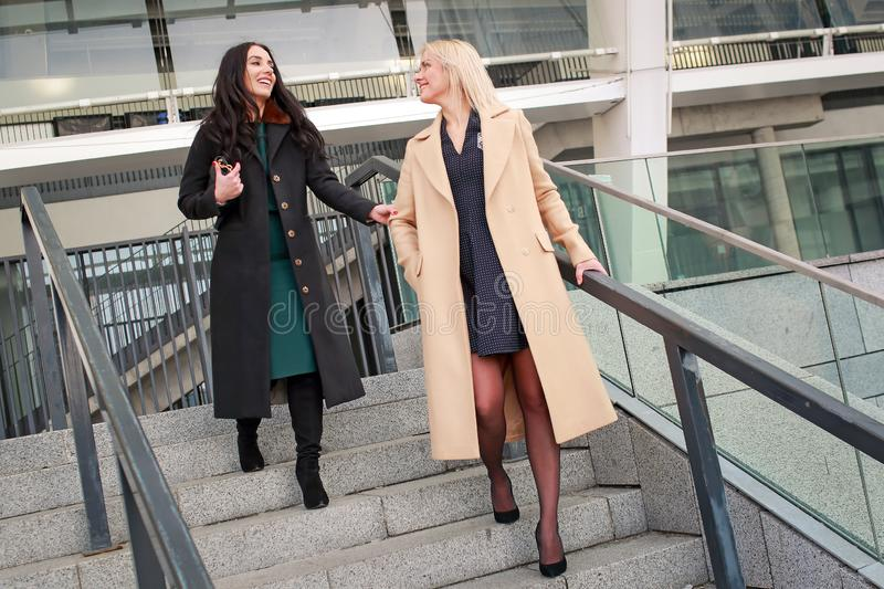 Two women walk in the city, drink coffee. And enjoy the rest royalty free stock image