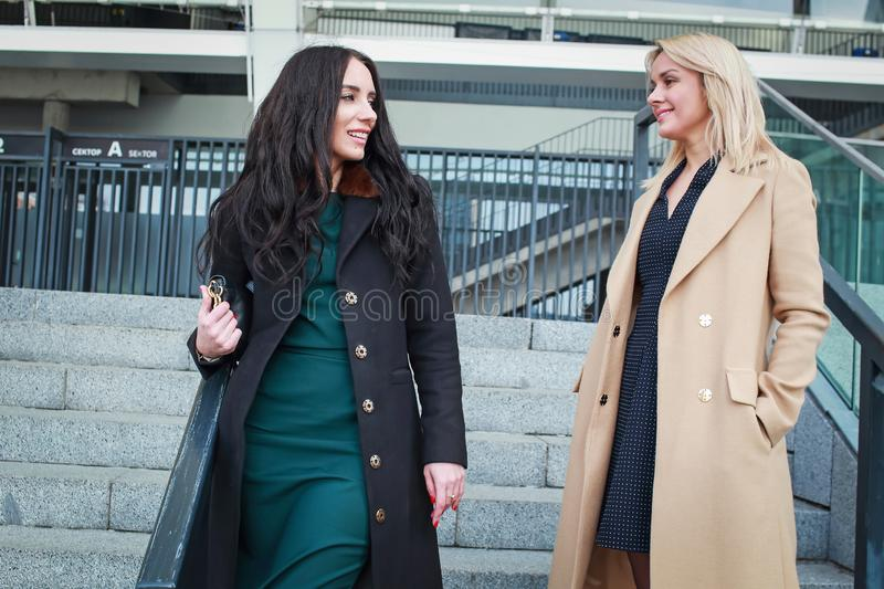 Two women walk in the city, drink coffee. And enjoy the rest royalty free stock photo
