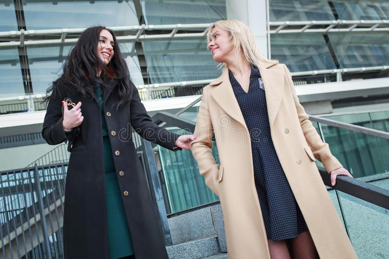 Two women walk in the city, drink coffee. And enjoy the rest stock photos